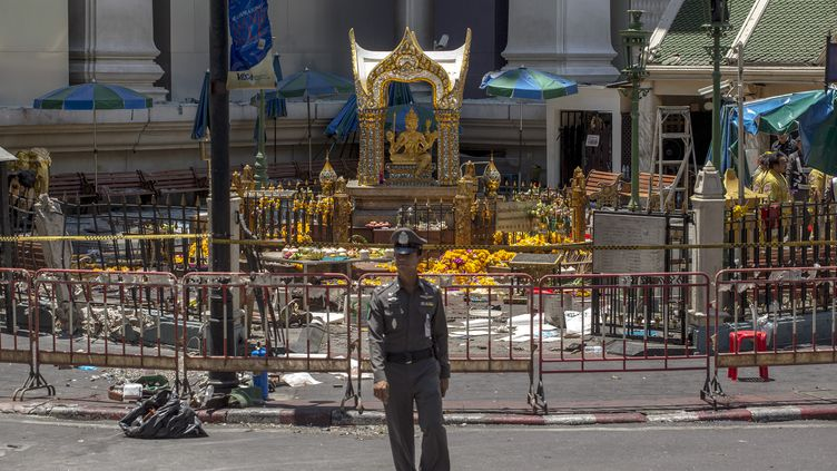 Un policier devant l'entrée du temps d'Erawan, mercredi 18 août 2015, à Bangkok (Thaïlande). (ATHIT PERAWONGMETHA / REUTERS)