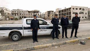 Des policiers libyens prennent la pose, le 15 février 2018, devant le palais de justice détruit de la ville de Benghazi, d'où étaient parties les premières manifestations contre le régime de l'ancien et défunt guide de la Jamahiriya libyenne, Mouammar Kadhafi. (Abdullah DOMA/AFP)