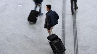 Un voyageur marche avec un bagage dans le hall de départ de la gare de Lyon à Paris, le 18 décembre 2020. (STEPHANE DE SAKUTIN / AFP)