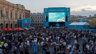 Des supporters russes regardent en direct le match de championnat de l'Euro 2021 entre la Russie et la Belgique le 12 juin 2021, dans la fan zone de la place Konyushennaya à Saint-Pétersbourg, en Russie. (MIKE KIREEV / AFP)