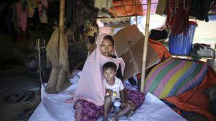 Sabikul Nahar, 21 ans, pose avec un enfant au camp de réfugié de Cox Bazar, Bangladesh, le 9 décembre 2017. (FIRAT YURDAKUL / ANADOLU AGENCY / AFP)
