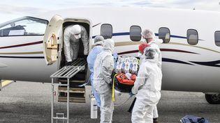 Une équipe médicale à Bron, près de Lyon (Rhône), récupère un malade du Covid-19 évacué d'un autre hôpital, le 27 octobre 2020. (PHILIPPE DESMAZES / AFP)