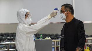 Un membre du personnel de sécurité vérifie la température d'un passager à l'aéroport international de Sanya Phoenix, dans la province de Hainan, au sud de la Chine, le 27 janvier 2020. (PU XIAOXU / XINHUA / AFP)