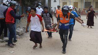 Un homme blessé porté par les secours lors d'une manifestation en Birmanie à Mandalay, le 20 février 2021. (AFP)
