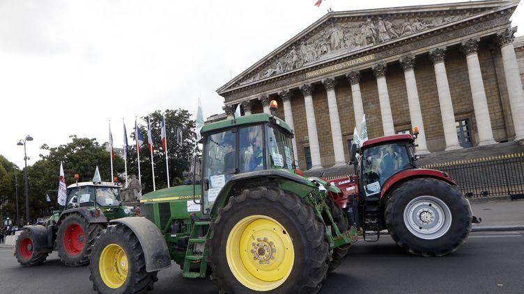 Un convoi de tracteurs passe devant l'Assemblée nationale. (THOMAS SAMSON / AFP)