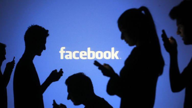 Des silhouettes regardant leurs téléphones devant un logo de Facebook, le 29 octobre 2014 à Zenica (Bosnie-Herzégovine). (© DADO RUVIC / REUTERS)