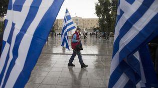 Un homme tient un drapeau grec près du Parlement, le 24 janvier 2015 à Athènes. (MARKO DJURICA / REUTERS)