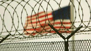 Un drapeau américain flotte derrière des barbelés sur la base de Guantanamo, à Cuba, le 26 juin 2006. (BRENNAN LINSLEY / AP / SIPA)