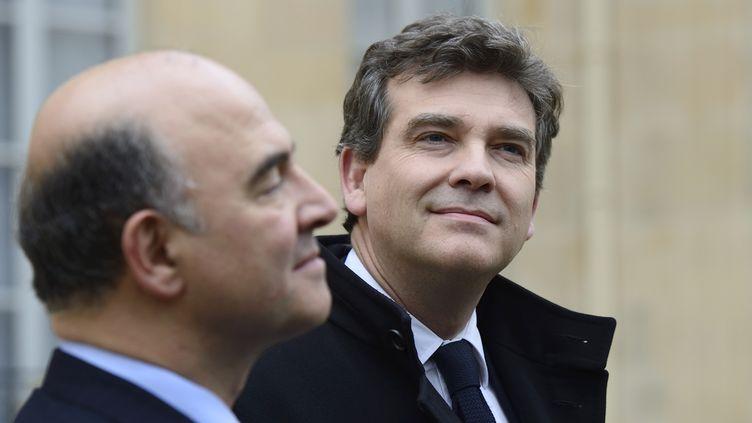 Les ministres de l'Economie et du Redressement productif,Pierre Moscovici (G) etArnaud Montebourg,dans la cour de l'Elysée (Paris) à la sortie du Conseil des ministres, le 27 novembre 2013. (ERIC FEFERBERG / AFP)