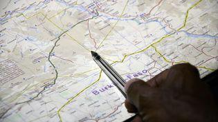 Un officiel Burkinabé montre la zone dans laquelle s'est vraisemblablement écrasé le vol AH5017, jeudi 24 juillet. (AHMED OUOBA / AFP)