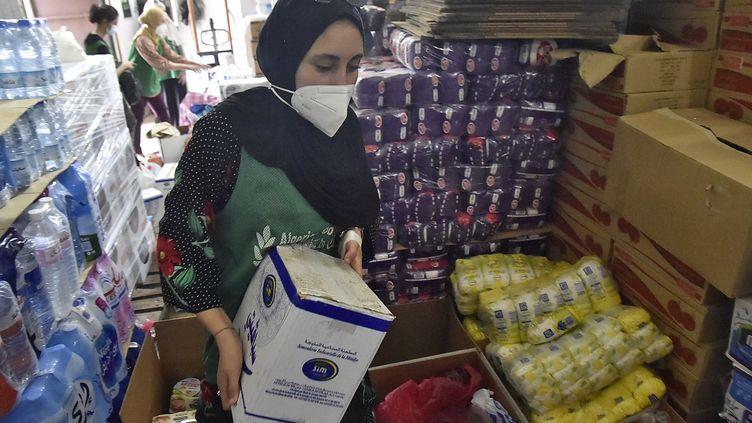 Des volontaires de l'association SIDRA participent à une initiative avec la Banque alimentaire algérienne pour envoyer des colis d'aide aux victimes des incendies de forêt en Kabylie dans la capitale algérienne Alger, le 12 août 2021. (RYAD KRAMDI / AFP)