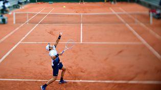 Le Français Elliot Benchetrit sert, lors du premier jour du tournoi de Roland-Garros, le 27 septembre 2020 à Paris, contre l'AméricainJohn Isner. (MARTIN BUREAU / AFP)