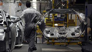 Un ouvrier de l'usine PSA de Sochaux-Montbéliard (Doubs) travaille sur une chaîne d'assemblage, le 18 mars 2009. (SEBASTIEN BOZON / AFP)