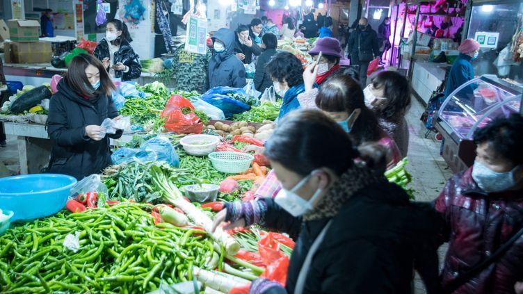 Des habitants de Wuhan (Chine) portentdes masques sur un marché, le 23 janvier 2020. (XIAO YIJIU / AFP)