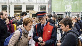 Un agent SNCF oriente des voyageurs, le 20 octobre 2019, gare de Lyon, à Paris. (DENIS MEYER / HANS LUCAS / AFP)