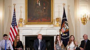 Donald Trump entouré d'étudiants et de professeurs lors d'une réunion sur les violences par armes à feu, à la Maison Blanche, à Washington, le 21 février 2018. (MANDEL NGAN / AFP)