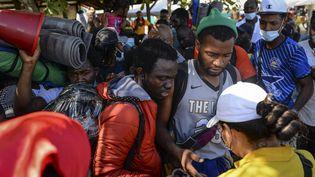 Des migrants haïtiens tentent d'embarquer sur un bâteau pour le Panama, le 13 septembre 2021, à Necocli (Colombie). (VANESSA JIMENEZ G. / ANADOLU AGENCY / AFP)