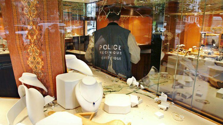 Un homme de la police scientifique enquête dans une bijouterie du 8e arrondissement de Paris, cible d'un braquage en 2002. (JACK GUEZ / AFP)