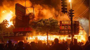 Des manifestants rassemblés devant un magasin d'alcool incendié, le 28 mai 2020 à Minneapolis (Minnesota). (KEREM YUCEL / AFP)
