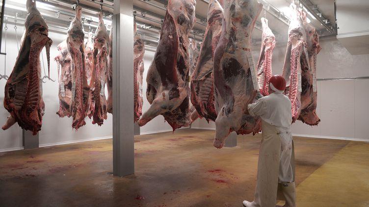 Un ouvrier de l'abattoir d'Haguenau (Bas-Rhin), travaille sur une carcasse de boeuf en juillet 2016. (FREDERICK FLORIN / AFP)