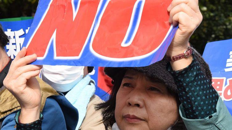 Une femme affiche son opposition à la construction d'une nouvelle base militaire américaine à Okinawa lors d'une manifestation devant la Diète (Parlement)à Tokyo, le 21 février 2016. Plusieurs centaines de personnes ont pris part à cette manifestation dénonçant le plan du gouvernement de laisser construire une base aérienne américaine en remplacement de celle de Futenma existant située dans une zone très peuplée. Les manifestations contre les bases d'Okinawa sont régulières au Japon. (TORU YAMANAKA / AFP)