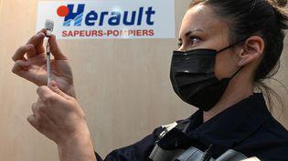 Une sapeur-pompier prépare une dose de vaccin àVailhauques près de Montpellier (Hérault) le 8 avril 2021. (PASCAL GUYOT / AFP)