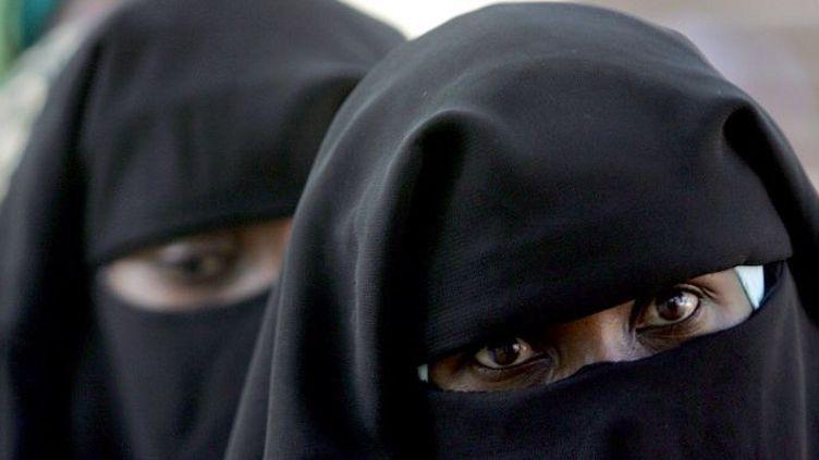 Tchadienne, revêtue de la Burqa, le voile intégral qui ne laisse voir que les yeux, faisant la queue devant un bureau de vote à N'Djamena le 3 mai 2006 pour le premier tour de la présidentielle. (AFP PHOTO/ISSOUF SANOGO)