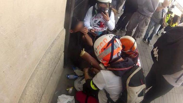 """Capture d'écran d'une vidéo montrant des personnes se présentant comme des """"street medics""""en train d'effectuer un prélèvement sanguin lors d'une manifestation de """"gilets jaunes"""", place de la République, le 20 avril 2019 à Paris. (FRANCEINFO)"""