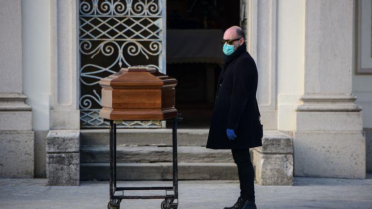 Un homme fait face au cercueil de sa mère lors de funérailles à Seriate, près de Bergame, en Italie, le 20 mars 2020. (PIERO CRUCIATTI / AFP)