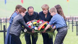 Francois Hollande etAngela Merkel déposant une gerbe de fleurs au cimetière de Consenvoye, le 29 mai 2016. (KAY NIETFELD / DPA / AFP)