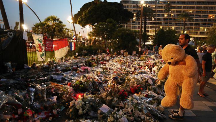 Un hommerend hommage aux victimes de l'attentat de Nice, le 19 juillet 2016 sur la Promenade des Anglais. (VALERY HACHE / AFP)