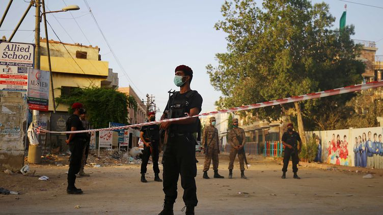Des forces de sécurité pakistanaises sécurisent la zone de Karachi où un avion s'est écrasé, samedi 23 mai 2020. (MAXPPP)