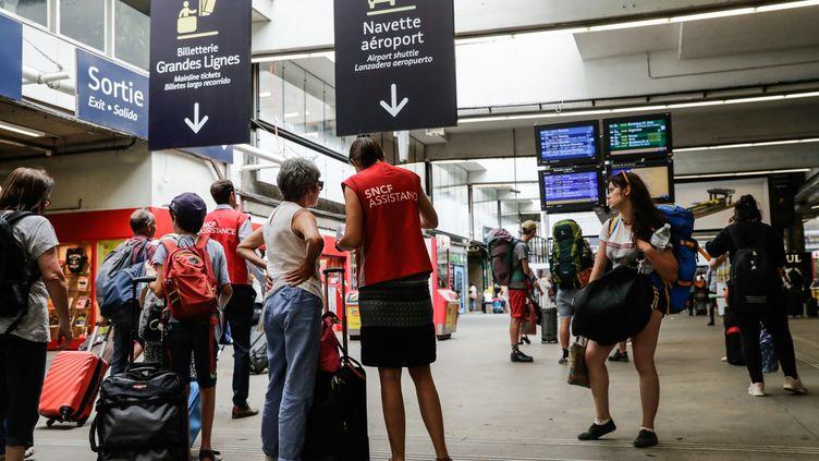 Des voyageurs attendent le départ de leur train, le 30 juillet 2018, à la gare Montparnasse à Paris. (THOMAS SAMSON / AFP)