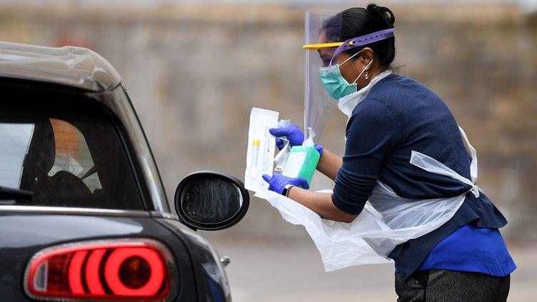 Une soignante présente un kit de test de Covid-19 à un automobiliste dans un drive de Londres le 25 avril 2020, pendant l'épidémie de coronavirus. (DANIEL LEAL-OLIVAS / AFP)