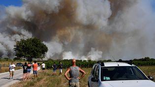 Des habitants de Vauvert (Gard), face à l'incendie, le 2 août 2019. (PASCAL GUYOT / AFP)