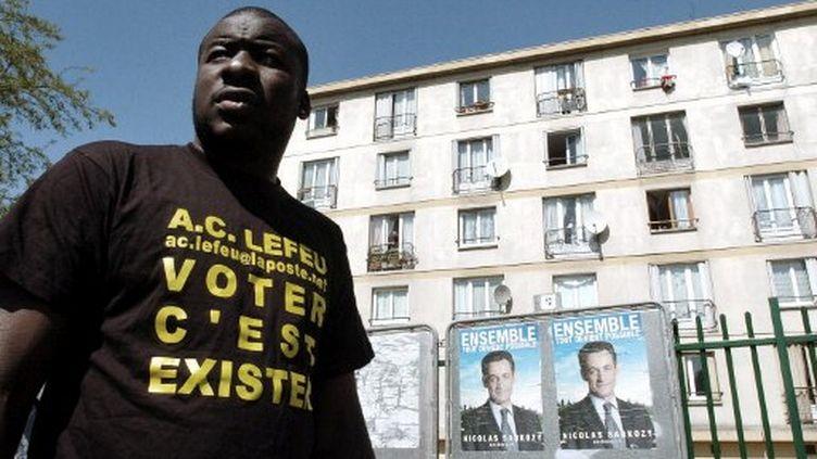 Un membre du collectif AC le Feu devant une affiche de campagne de 2007 à Clichy-sous-Bois (photo d'illustration) (JEAN AYISSI / AFP)