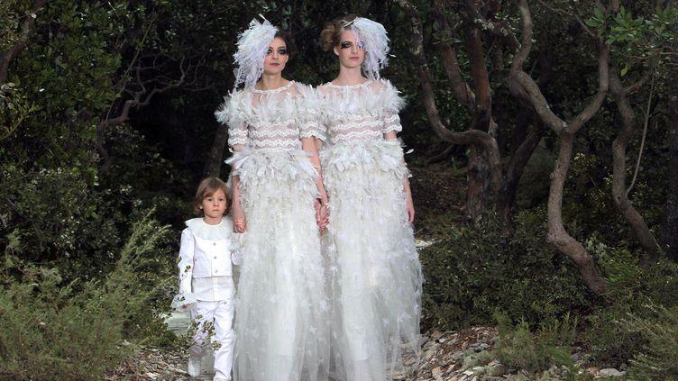 Deux femmes en robe de mariée accompagnées par un enfant en clôture du défilé Chanel, le mardi 22 janvier 2013. (LOIC VENANCE / AFP)