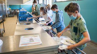Des collégiens débarrassent leurs plateaux de cantine, le 2 juin 2020, à Beaucamps-Ligny (Nord). (JULIE SEBADELHA / HANS LUCAS / AFP)