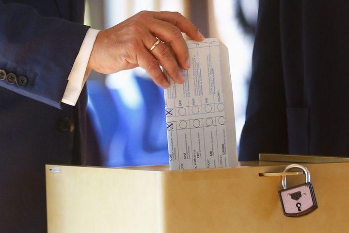 Le candidat de la CDU, Amin Laschet, vote en pliant son bulletin à l'envers, à Aix-la-Chapelle, en Allemagne, lors des élections législatives, dimanche 26 septembre 2021. (FRANCK FIFE / AFP)