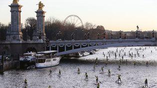"""Des centaines de personnes descendent la Seine en """"paddle"""" à l'occasion du salon Nautique à Paris, le 6 décembre 2014. (THOMAS SAMSON / AFP)"""