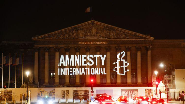 Le logode l'ONG Amnesty International projeté sur lePalais Bourbon à Paris, le 18 juin 2018. (GEOFFROY VAN DER HASSELT / AFP)