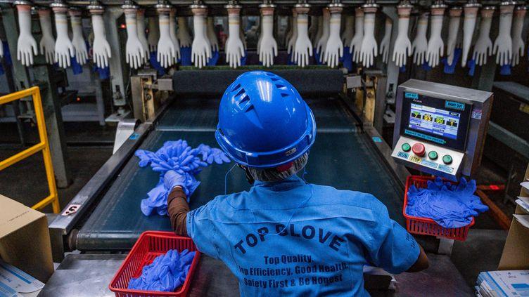 Un travailleur inspecte des gants jetables à l'usine Top Glove à Shah Alam, dans la banlieue de Kuala Lumpur,le 26 août 2020 (photo d'illustration). (MOHD RASFAN / AFP)