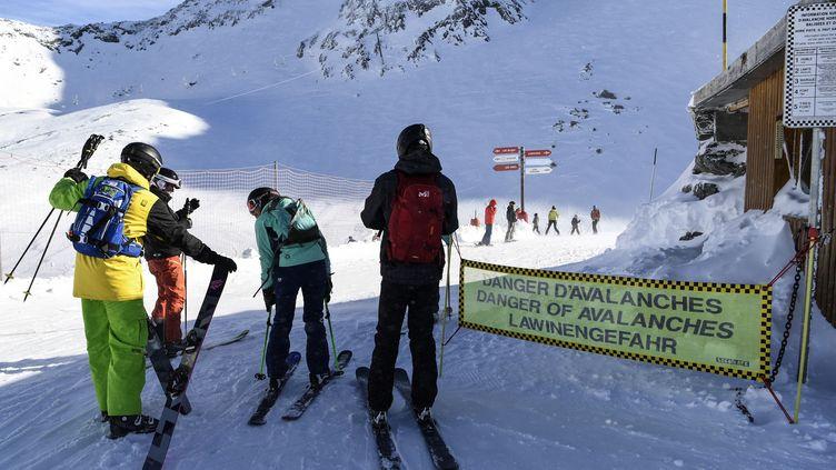 Des skieurs passent devant une banderole de vigilance pour les avalanches, le 6 janvier 2018, à Val-Thorens (Savoie). (PHILIPPE DESMAZES / AFP)