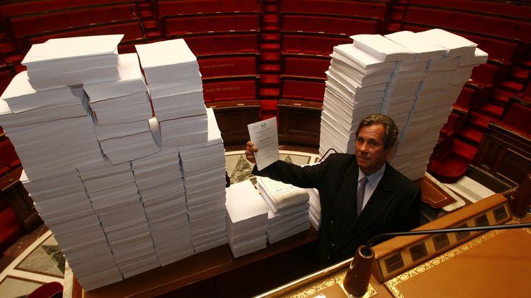 Jean-Louis Debré, alors président UMP de l'Assemblée nationale, pose devant 137 665 amendements contre le projet de loi sur la fusion GDF-Suez, le 5 septembre 2006. (OLIVIER LEJEUNE / MAXPPP)