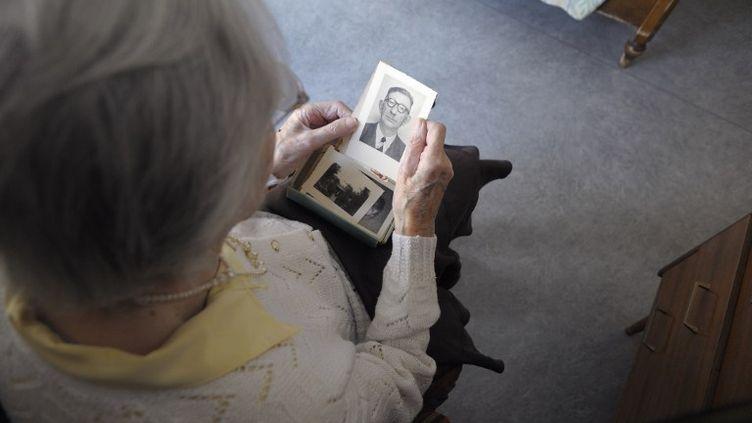 Une femme atteinte de la maladie d'Alzheimer regarde une photo, dans une maison de retraite d'Angervilliers (Essonne), le 18 mars 2011. (SEBASTIEN BOZON / AFP)