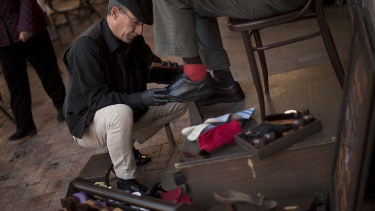 Javier Castano cire les chaussures d'un client, le 16 février 2015, à Malaga (Espagne). (JORGE GUERRERO / AFP)
