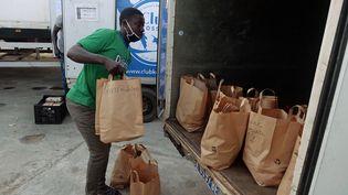 A Dakar, un employé du Club Kossam, entreprise de livraison d'alimentation achetée en ligne, charge un camion avec les commandes des internautes. (CHRISTOPHE VAN DER PERRE / REUTERS)