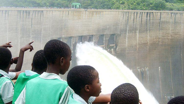 Des jeunes Zambiens devant le barrage de Kariba en Zambie, le 12 février 2008. Ce barrage hydroélectrique commun à la Zambie et au Zimbabwe a été inauguré en janvier 1959. (COLLINS PHIRI / AFP)