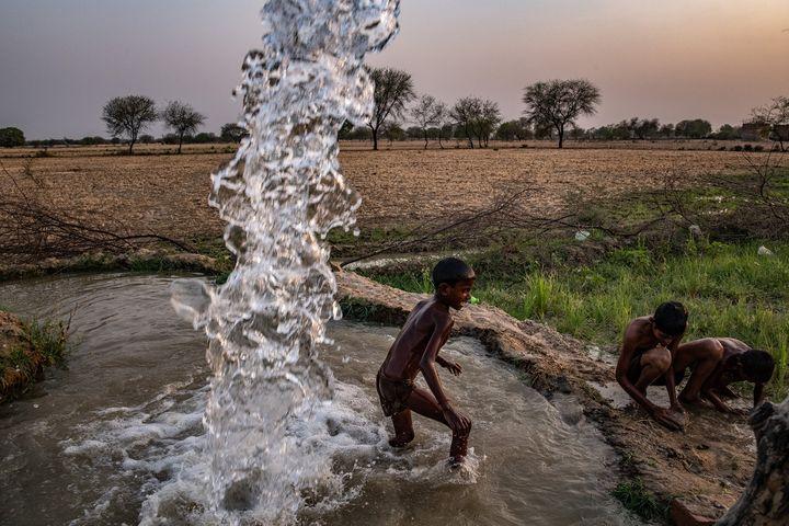 """Des enfants jouent dans l'eau d'un forage privé, en Inde. Une photo de Bryan Denton dans le cadre de l'exposition """"Sécheresse et déluge : comment le changement climatique modifie la mousson en Inde"""". (Bryan Denton for The New York Times)"""