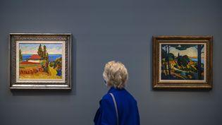 """Un visiteur devant les toiles """"Paysageà Cassis"""" de Derain et """"Paysage en Corse"""" d'Herbinlors d'une exposition à Potsdam. (JOHN MACDOUGALL / AFP)"""